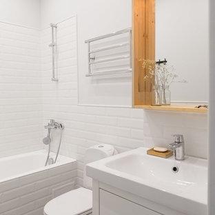 На фото: маленькая главная ванная комната в скандинавском стиле с белыми фасадами, раздельным унитазом, белой плиткой, керамической плиткой, душем над ванной, белыми стенами и монолитной раковиной с