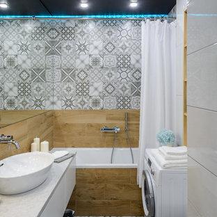 Свежая идея для дизайна: маленькая главная ванная комната в белых тонах с отделкой деревом в современном стиле с плоскими фасадами, белыми фасадами, душем над ванной, керамогранитной плиткой, полом из керамогранита, столешницей из ламината, серым полом, шторкой для ванной, серой столешницей, ванной в нише, серой плиткой и настольной раковиной - отличное фото интерьера