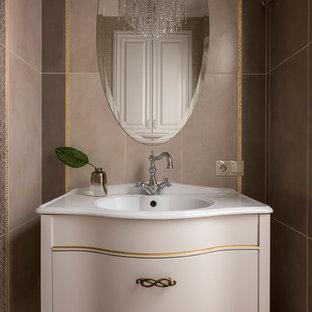 На фото: ванная комната в стиле неоклассика (современная классика) с бежевыми фасадами, бежевой плиткой, коричневой плиткой, монолитной раковиной и белой столешницей