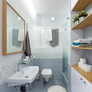 Неиссякаемый источник вдохновения для домашнего уюта: ванная комната среднего размера в современном стиле с плоскими фасадами, белыми фасадами, душем в нише, инсталляцией, серой плиткой, керамической плиткой, серыми стенами, полом из керамической плитки, душевой кабиной, подвесной раковиной, серым полом и душем с распашными дверями