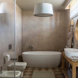 На фото: главные ванные комнаты в средиземноморском стиле с открытыми фасадами, отдельно стоящей ванной, биде, бежевыми стенами и настольной раковиной