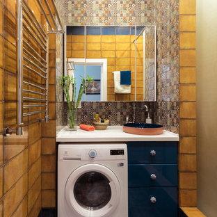 Immagine di una stanza da bagno con doccia bohémian di medie dimensioni con ante lisce, ante blu, doccia alcova, piastrelle arancioni, piastrelle in ceramica, pavimento con piastrelle in ceramica, lavabo da incasso, top in superficie solida, pavimento multicolore e lavanderia