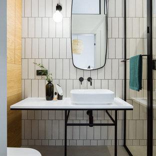Пример оригинального дизайна: ванная комната в современном стиле с белой плиткой, бетонным полом, настольной раковиной, серым полом, белой столешницей и тумбой под одну раковину