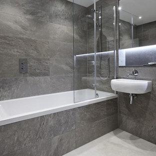 Imagen de cuarto de baño principal, contemporáneo, de tamaño medio, con bañera empotrada, sanitario de pared, baldosas y/o azulejos de travertino, suelo de mármol, lavabo suspendido, encimera de cuarzo compacto y suelo blanco