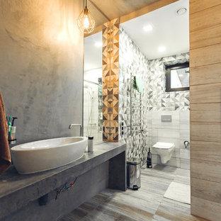 Idee per una stanza da bagno con doccia industriale di medie dimensioni con doccia ad angolo, WC sospeso, piastrelle multicolore, piastrelle in ceramica, pareti grigie, pavimento con piastrelle in ceramica, lavabo a bacinella, top in cemento, pavimento marrone, porta doccia scorrevole e top grigio