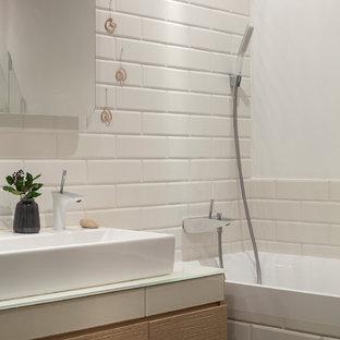 Новый формат декора квартиры: главная ванная комната в современном стиле с плоскими фасадами, светлыми деревянными фасадами, ванной в нише, душем над ванной, плиткой кабанчик, настольной раковиной и стеклянной столешницей