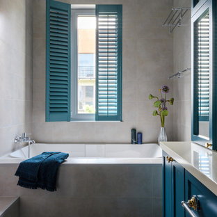 Свежая идея для дизайна: главная ванная комната среднего размера в стиле современная классика с серой плиткой, керамогранитной плиткой, полом из керамогранита, столешницей из искусственного камня, разноцветным полом, бежевой столешницей, ванной в нише, фасадами в стиле шейкер, синими фасадами и серыми стенами - отличное фото интерьера