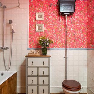 Bild på ett mellanstort vintage badrum för barn, med skåp i slitet trä, ett badkar i en alkov, en dusch/badkar-kombination, vit kakel, släta luckor, en toalettstol med separat cisternkåpa, röda väggar, mörkt trägolv och dusch med duschdraperi