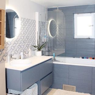 Стильный дизайн: ванная комната в скандинавском стиле с плоскими фасадами, полновстраиваемой ванной, инсталляцией, синей плиткой, керамической плиткой, белыми стенами, полом из керамической плитки, монолитной раковиной, столешницей из искусственного камня, бежевым полом и белой столешницей - последний тренд
