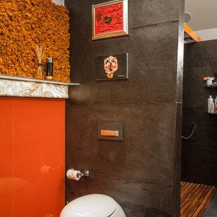 Diseño de cuarto de baño con ducha, industrial, de tamaño medio, con sanitario de pared, baldosas y/o azulejos naranja, baldosas y/o azulejos de vidrio, paredes negras, suelo de baldosas de porcelana, suelo negro, ducha abierta, armarios con paneles lisos y ducha abierta