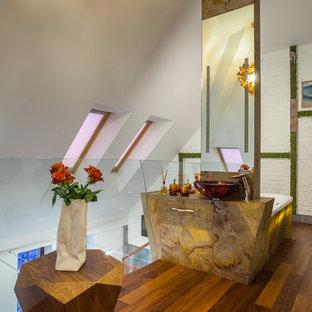 На фото: большая главная ванная комната в стиле лофт с настольной раковиной, коричневым полом, плоскими фасадами, желтыми фасадами, угловой ванной, желтой плиткой, плиткой из сланца, столешницей из оникса, душем над ванной, белыми стенами и темным паркетным полом с