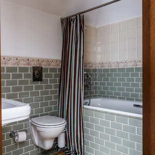 Mediterranean ensuite bathroom in Other with an alcove bath, a shower/bath combination, a wall mounted toilet, green tiles, metro tiles, white walls, a wall-mounted sink, yellow floors and a shower curtain.