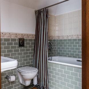 На фото: главная ванная комната в средиземноморском стиле с ванной в нише, душем над ванной, инсталляцией, зеленой плиткой, плиткой кабанчик, белыми стенами, подвесной раковиной, желтым полом и шторкой для душа с