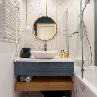 На фото: главная ванная комната в современном стиле с плоскими фасадами, серыми фасадами, ванной в нише, душем над ванной, белой плиткой, белыми стенами, настольной раковиной, белым полом и белой столешницей