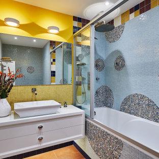 На фото: ванная комната среднего размера в современном стиле с фасадами с утопленной филенкой, белыми фасадами, ванной в нише, душем над ванной, синей плиткой, разноцветной плиткой, желтой плиткой, желтыми стенами, душевой кабиной, настольной раковиной, оранжевым полом, душем с раздвижными дверями и белой столешницей с