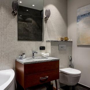 Ispirazione per una stanza da bagno padronale contemporanea con ante lisce, ante in legno bruno, vasca ad angolo, WC sospeso, piastrelle grigie, lavabo sottopiano, top in granito, pavimento grigio e top grigio