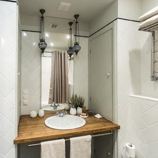 Ejemplo de cuarto de baño principal, pequeño, con bañera encastrada, combinación de ducha y bañera, sanitario de pared, baldosas y/o azulejos blancos, baldosas y/o azulejos de cerámica, paredes grises, suelo de pizarra, lavabo encastrado y encimera de madera