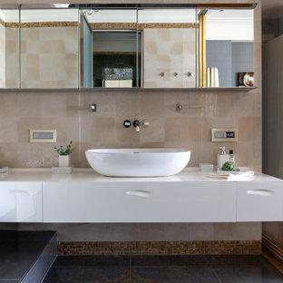На фото: большая главная ванная комната в современном стиле с плоскими фасадами, белыми фасадами, бежевой плиткой, настольной раковиной, черным полом, белой столешницей, тумбой под одну раковину и подвесной тумбой