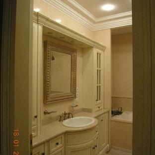 Esempio di una stanza da bagno padronale vittoriana di medie dimensioni con ante con riquadro incassato, ante beige, vasca sottopiano, WC a due pezzi, piastrelle beige, piastrelle in ceramica, pareti beige, pavimento in gres porcellanato, lavabo rettangolare, top in marmo, pavimento multicolore e top beige