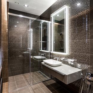 На фото: со средним бюджетом ванные комнаты среднего размера в современном стиле с плоскими фасадами, серыми фасадами, душем без бортиков, биде, коричневой плиткой, керамической плиткой, коричневыми стенами, полом из керамогранита, душевой кабиной, накладной раковиной, столешницей из искусственного камня, коричневым полом, душем с раздвижными дверями и серой столешницей