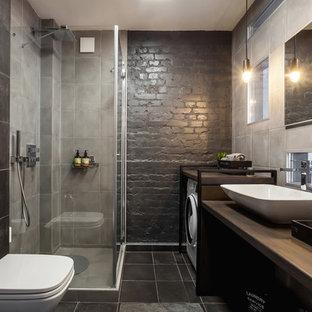 Стильный дизайн: ванная комната среднего размера в современном стиле с серой плиткой, керамогранитной плиткой, черными стенами, полом из керамической плитки, душевой кабиной, настольной раковиной, столешницей из дерева, черным полом, душем с распашными дверями, угловым душем, инсталляцией и коричневой столешницей - последний тренд