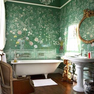 На фото: главная ванная комната в викторианском стиле с ванной на ножках, зелеными стенами, раковиной с пьедесталом и коричневым полом