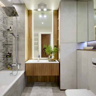 Идея дизайна: главная ванная комната в современном стиле с плоскими фасадами, фасадами цвета дерева среднего тона, ванной в нише, душем над ванной, инсталляцией, серой плиткой, серым полом, белой столешницей, серыми стенами и подвесной раковиной