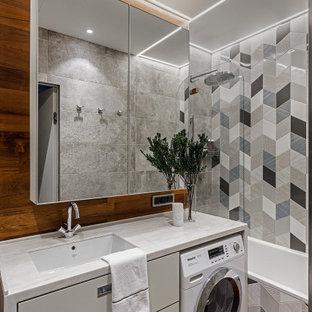 На фото: ванная комната среднего размера в современном стиле с белыми фасадами, ванной в нише, врезной раковиной, белой столешницей, коричневым полом, душем над ванной, паркетным полом среднего тона, тумбой под одну раковину, плоскими фасадами, инсталляцией, серой плиткой, керамогранитной плиткой, разноцветными стенами, столешницей из искусственного кварца, стиральной машиной, встроенной тумбой и деревянными стенами