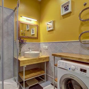 Cette photo montre une salle d'eau tendance avec un placard sans porte, une douche d'angle, un carrelage gris, un mur jaune, un plan de toilette en bois, un sol multicolore, une cabine de douche à porte coulissante et un plan de toilette marron.