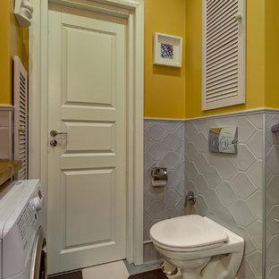Esempio di una stanza da bagno design con WC sospeso, pareti gialle e pavimento multicolore