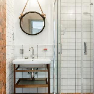 На фото: ванная комната в современном стиле с душевой кабиной, консольной раковиной и коричневым полом с
