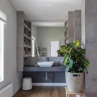 На фото: ванные комнаты в современном стиле с серой плиткой, серыми стенами, паркетным полом среднего тона, настольной раковиной, коричневым полом и серой столешницей