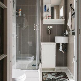 На фото: ванная комната в современном стиле с плоскими фасадами, белыми фасадами, угловым душем, коричневой плиткой, серой плиткой, душевой кабиной, подвесной раковиной, белым полом и душем с раздвижными дверями с