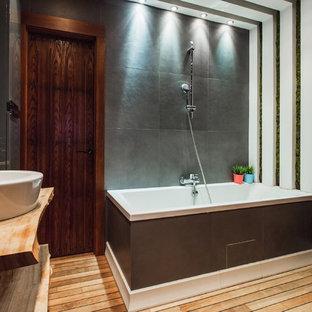 Неиссякаемый источник вдохновения для домашнего уюта: главная ванная комната в современном стиле с открытыми фасадами, душем над ванной, серой плиткой, деревянным полом, настольной раковиной, коричневым полом и столешницей из дерева