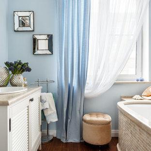 Diseño de cuarto de baño principal, costero, con armarios con puertas mallorquinas, puertas de armario blancas, bañera encastrada sin remate, baldosas y/o azulejos beige, baldosas y/o azulejos en mosaico, paredes azules, lavabo encastrado, suelo marrón, encimeras beige y encimera de piedra caliza