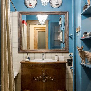 Новые идеи обустройства дома: главная ванная комната в стиле фьюжн с темными деревянными фасадами, душем над ванной, белой плиткой, синими стенами, накладной раковиной, столешницей из дерева, коричневым полом, шторкой для душа и коричневой столешницей