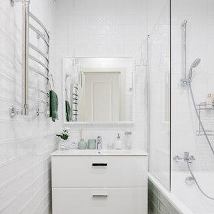 Пример оригинального дизайна: маленькая главная ванная комната в современном стиле с плоскими фасадами, белыми фасадами, ванной в нише, душем над ванной, белой плиткой, зеленой плиткой и монолитной раковиной