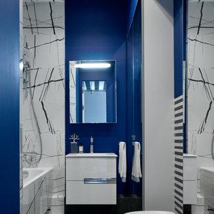 Идея дизайна: ванная комната среднего размера в современном стиле с плоскими фасадами, белыми фасадами, ванной в нише, душем над ванной, инсталляцией, черно-белой плиткой, синими стенами, полом из керамогранита, врезной раковиной, черным полом, открытым душем и белой столешницей