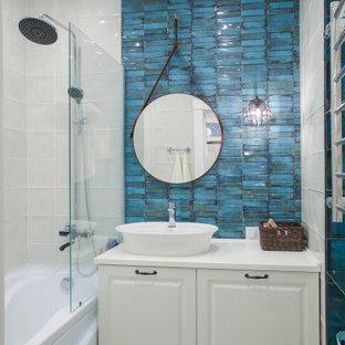 Стильный дизайн: главная ванная комната среднего размера в стиле неоклассика (современная классика) с керамической плиткой, настольной раковиной, столешницей из искусственного камня, белой столешницей, фасадами с выступающей филенкой, белыми фасадами, душем над ванной, бежевой плиткой, синей плиткой, открытым душем, тумбой под одну раковину, ванной в нише и напольной тумбой - последний тренд