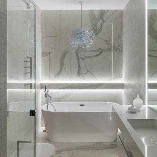 На фото: главная ванная комната в современном стиле с отдельно стоящей ванной и монолитной раковиной
