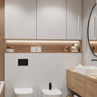 Bild på ett mellanstort minimalistiskt beige beige en-suite badrum, med släta luckor, skåp i mellenmörkt trä, ett undermonterat badkar, en vägghängd toalettstol, grå kakel, porslinskakel, grå väggar, klinkergolv i keramik, ett fristående handfat, träbänkskiva, vitt golv och dusch med duschdraperi