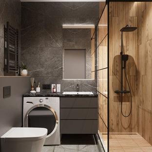 Mittelgroßes Modernes Duschbad mit flächenbündigen Schrankfronten, grauen Schränken, Duschnische, Wandtoilette, grauen Fliesen, Porzellanfliesen, grauer Wandfarbe, Porzellan-Bodenfliesen, Unterbauwaschbecken, Mineralwerkstoff-Waschtisch, grauem Boden, Duschvorhang-Duschabtrennung, schwarzer Waschtischplatte, Wäscheaufbewahrung, Einzelwaschbecken und schwebendem Waschtisch in Sonstige