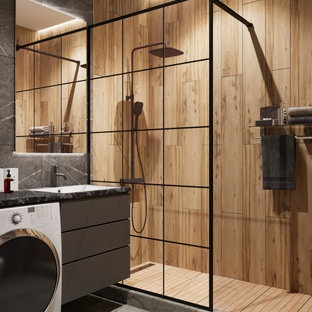 This is an example of a mid-sized industrial 3/4 bathroom in Other with flat-panel cabinets, grey cabinets, an alcove shower, a wall-mount toilet, gray tile, porcelain tile, grey walls, porcelain floors, an undermount sink, solid surface benchtops, grey floor, a shower curtain, black benchtops, a laundry, a single vanity and a floating vanity.