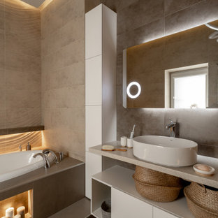 Idéer för ett modernt beige badrum, med släta luckor, vita skåp, ett platsbyggt badkar, beige kakel, ett fristående handfat och grått golv