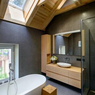 Inspiration för ett mellanstort orientaliskt beige beige badrum med dusch, med släta luckor, skåp i ljust trä, ett fristående badkar, grå kakel, ett fristående handfat, träbänkskiva, grått golv, med dusch som är öppen och en hörndusch