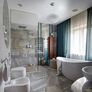 На фото: ванная комната в современном стиле с отдельно стоящей ванной, угловым душем, биде, бежевой плиткой, серой плиткой, серыми стенами, душевой кабиной, настольной раковиной, серым полом и душем с распашными дверями с