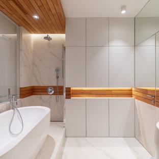 На фото: большая главная ванная комната в белых тонах с отделкой деревом в современном стиле с отдельно стоящей ванной, душевой комнатой, белой плиткой, белыми стенами, белым полом и открытым душем с
