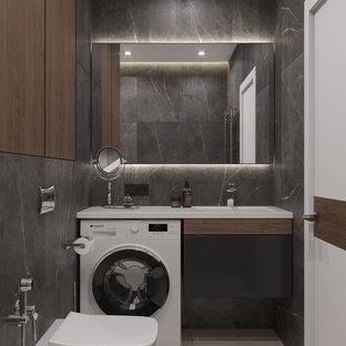 Bild på ett litet funkis vit vitt en-suite badrum, med släta luckor, svarta skåp, en vägghängd toalettstol, grå väggar, ett integrerad handfat, bänkskiva i akrylsten, grått golv, dusch med duschdraperi, ett undermonterat badkar, svart kakel, porslinskakel och klinkergolv i porslin