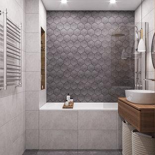 Inspiration för ett mellanstort funkis brun brunt en-suite badrum, med släta luckor, skåp i mellenmörkt trä, ett undermonterat badkar, en vägghängd toalettstol, grå kakel, keramikplattor, grå väggar, ett fristående handfat, träbänkskiva, grått golv, dusch med duschdraperi och klinkergolv i porslin