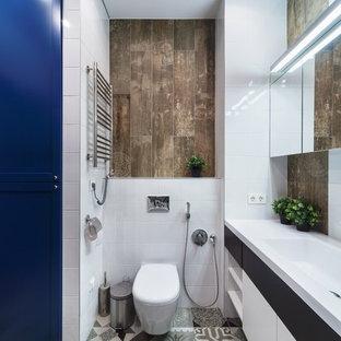 Неиссякаемый источник вдохновения для домашнего уюта: главная ванная комната среднего размера в современном стиле с инсталляцией, белой плиткой, коричневой плиткой, фасадами с выступающей филенкой, синими фасадами, ванной в нише, керамогранитной плиткой, белыми стенами, полом из керамогранита, врезной раковиной, столешницей из искусственного камня, серым полом и шторкой для душа